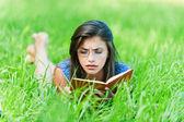 Woman lying down reading book — Stock Photo