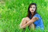 Sad woman sitting on grass — Stock Photo
