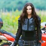 Portrait beautiful sad woman standing alongside red motorcycle — Stock Photo