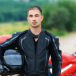 Portrait nice young man helmet beside motorcycle — Stock Photo