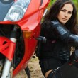 Portrait beautiful young woman leaning motorcycle — Stock Photo
