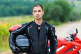 Portrait nice young man helmet beside motorcycle — Stock Photo