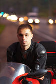 Portrait young attractive male sitting motorcyclist — Stock Photo