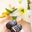 Two chocolate cakes with blooming lilies - Stock Photo