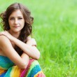 Stock Photo: Young beautiful woman sitting on grass