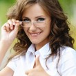 Portrait charming young woman glasses shows sign victory — Stock Photo
