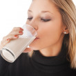 hermosa joven bebiendo leche aislada sobre fondo blanco — Foto de Stock