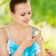 Woman examining with a magnifying glass flower — Stock Photo