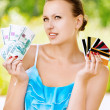 Woman holding credit cards and cash — Stock Photo
