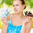 Woman holding credit cards and cash - Stock Photo