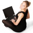 Smiling yong woman sitting on floor with laptop isolated on whit — Stock Photo