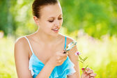 Woman examining with a magnifying glass flower — Stockfoto