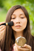 Portrait of young beautiful asian girl looks mirror powder — Stock Photo