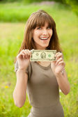Young smiling woman holding two dollars — Stockfoto