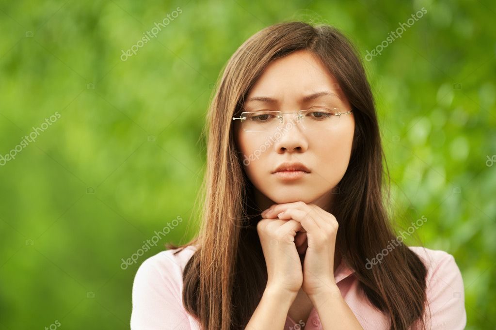Portrait of a sad asian girl wearing eyeglasses at summer green park — Stock Photo #8956803