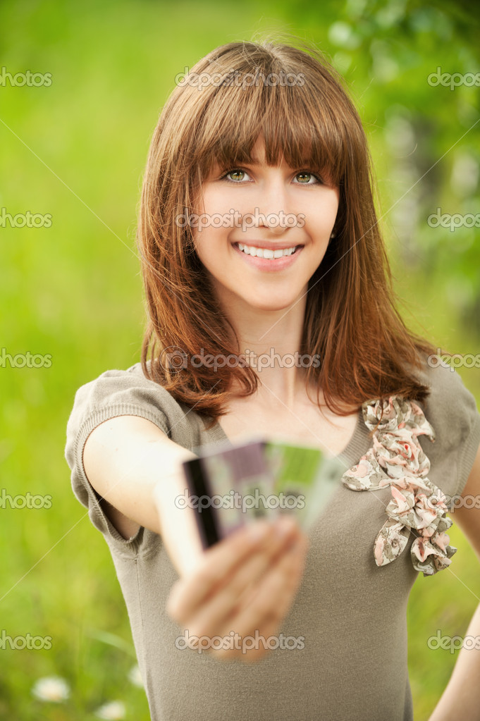 Portrait of young smiling woman holding several credit cards at summer green park — Photo #8957312