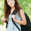 Portrait of young woman with black backpack - Foto Stock