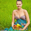 Woman holding a basket of fruit sits on grass — Stock Photo
