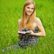 Young woman sits on grass and reading book — Stock Photo #9229064