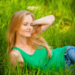 Portrait young woman lying green grass — Stock Photo