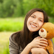 Young woman with teddy bear - Stockfoto