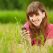 Young woman with mobile phone lies on green grass — Stock Photo #9230406