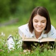 Young woman lies on grass and reads book — Stock Photo #9230658