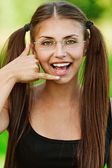 Portrait of young woman speaking on imaginary phone — Stock Photo