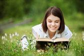 Giovane donna si trova sull'erba e legge il libro — Foto Stock