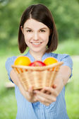 Young woman holding a basket of fruit — Stock Photo