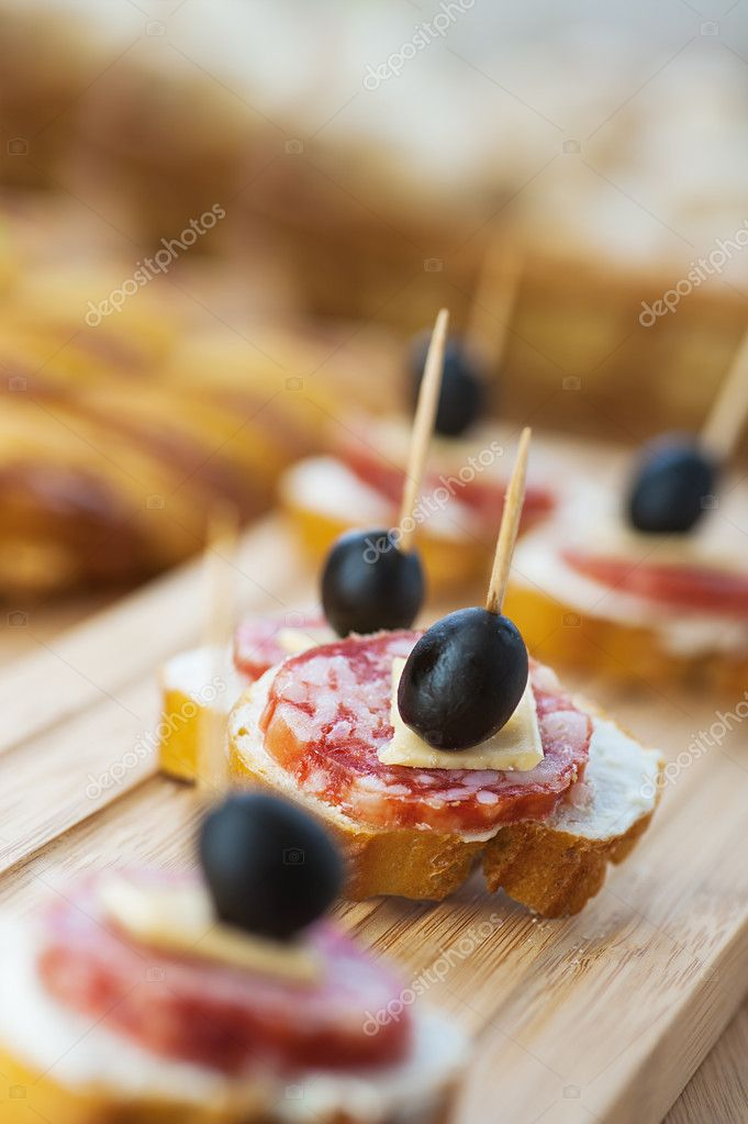 Sausage sandwiches, cheese and olives on toothpick, wooden table in background.  Stock Photo #9550781