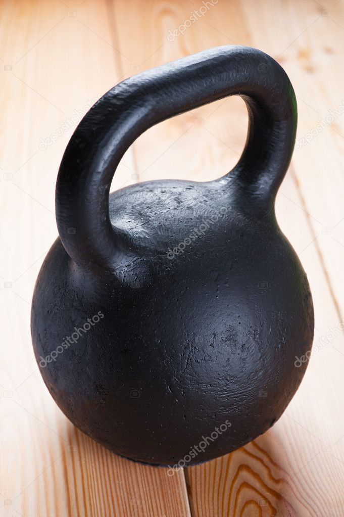 Large black cast iron weight on wooden floor in gym. — Stock Photo #9550797