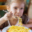 Small girl eating spaghetti — Stok fotoğraf