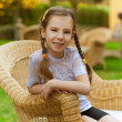Little girl sits in wicker chair — Stock Photo