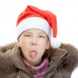 Little girl in Christmas hat show tongue — Stock Photo
