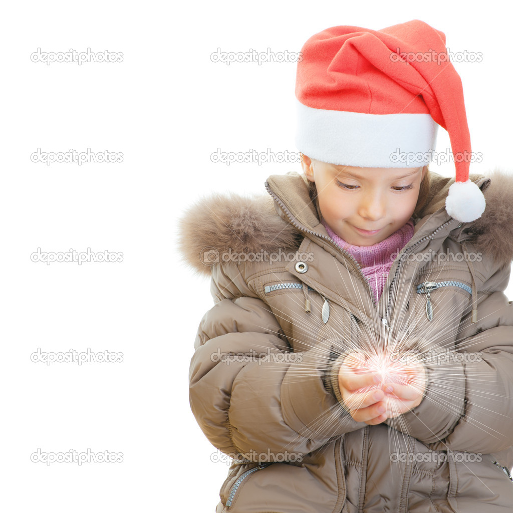 Little girl in jacket and Christmas hat keeps shining ball, isolated on white background. — Stock Photo #9579108