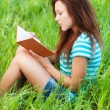 Young woman sits on grass and reading book — Stock Photo #9580548