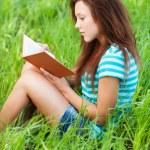 genç kadın çim ve okuma kitabı üzerinde oturur — Stok fotoğraf