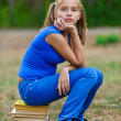 Teenager girl sitting on stack books — Stock Photo #9793829