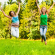 Two young beautiful girls jumps up at summer green park — Stock Photo #9794563