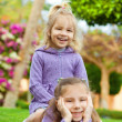 Two sisters playing on green meadow — Stock Photo #9794771