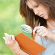 Young woman magnifier regards book — Stock Photo #9795246