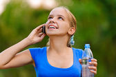 Smiling teenager girl with bottle talking on phone — Stock Photo