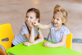 Two sisters sitting at green table — Stock Photo