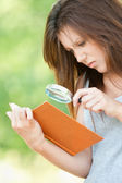 Young woman magnifier regards book — 图库照片