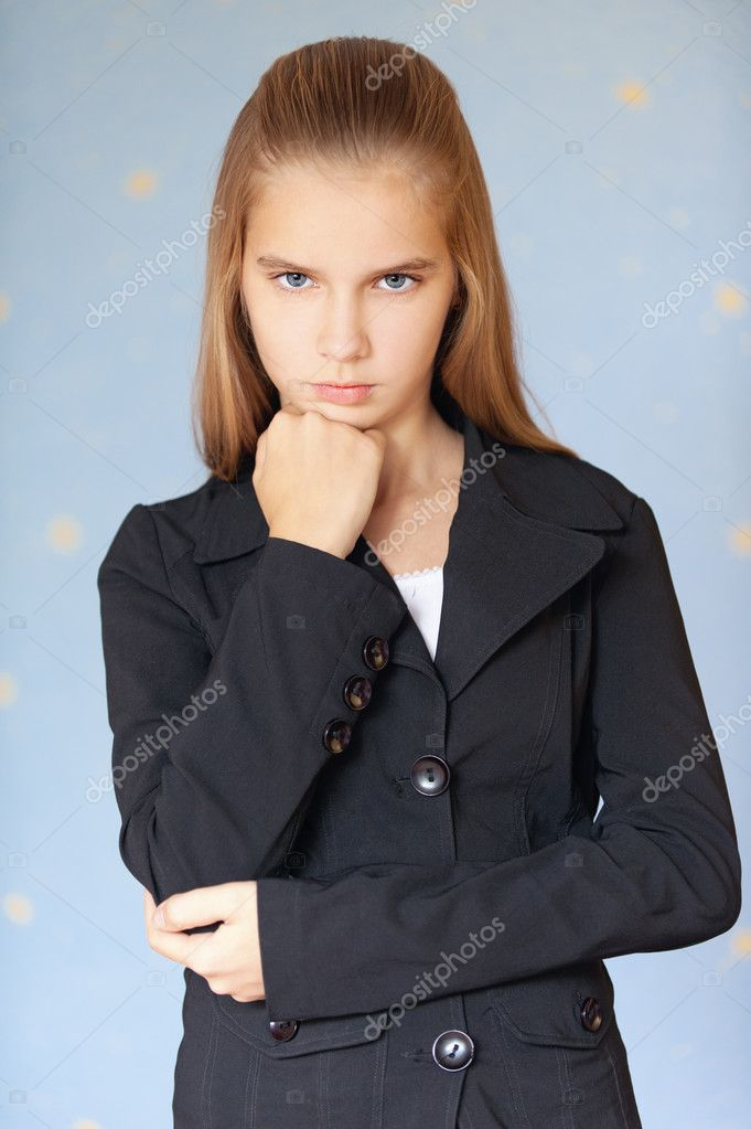 Serious girl-teenager in business suit propped his chin with his fist, on blue background. — Stock Photo #9793849
