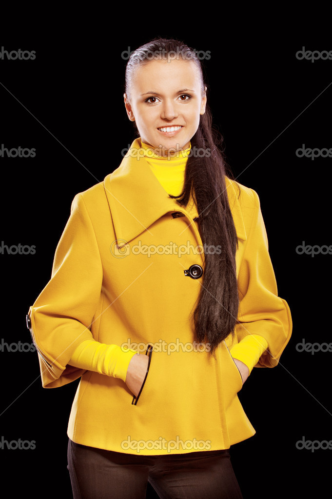 Portrait of smiling young beautiful woman in yellow coats and long hair, isolated on black background. — Stock Photo #9875566