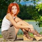 Beautiful woman sitting on shore of lake — Stock Photo