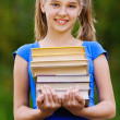 Teenager girl holding stack of seven books — Stock Photo