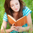 Young woman sits on grass and reading book — Stock Photo